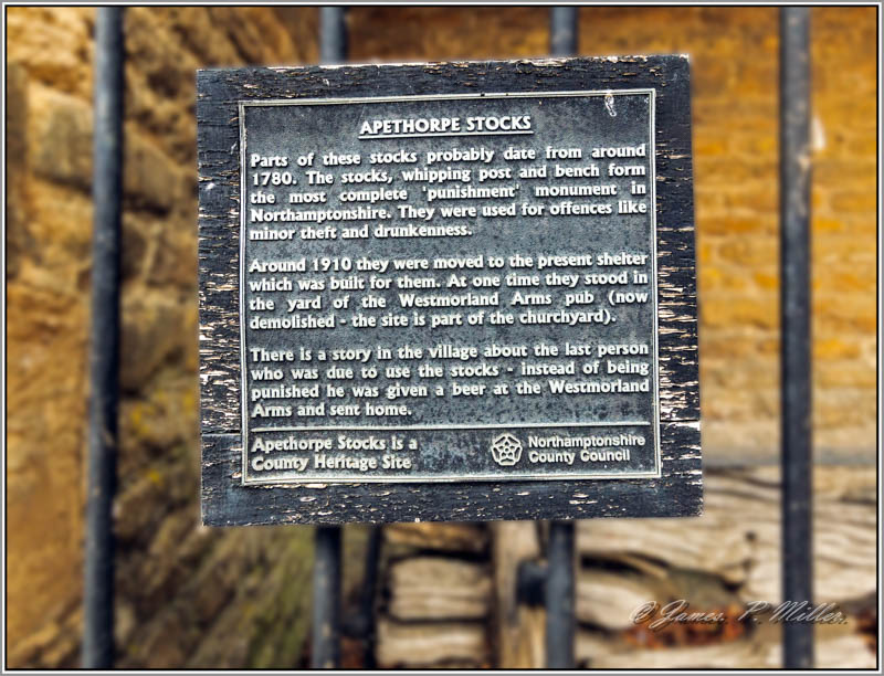 Sign on Apethorpe Village Stocks and Whipping Post, Apethorpe, Northamptonshire, England.